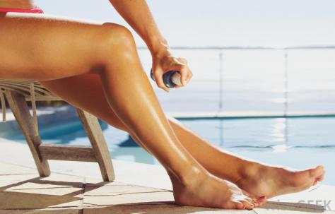 woman-using-spray-tan-on-legs